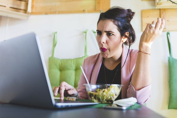 Young businesswoman having healthy lunch and using laptop