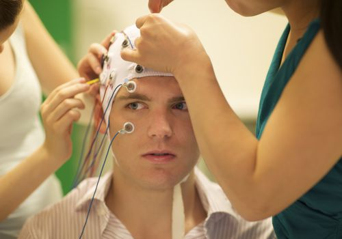 women applying sensors to man's head