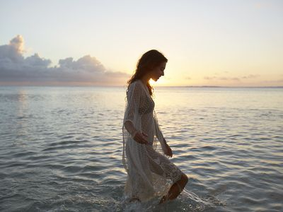 Brunette woman wearing swimsuit smiles and wades in the ocean at sunset