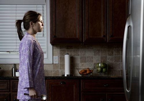 Woman in pyjamas, looking at refrigerator
