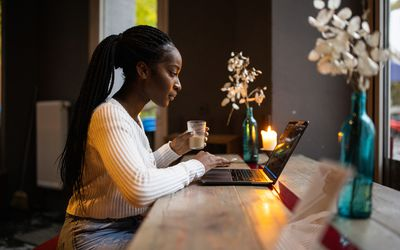 african american woman sitting at her computer with flowers and a candle