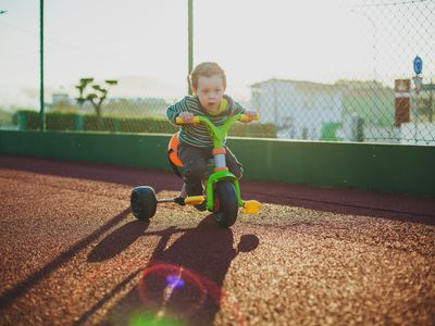 boy playing on tricicle outdoors
