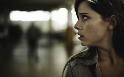 woman nervously looking behind her in public place