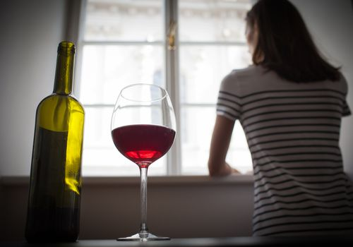 woman looking out window with glass of wine on table