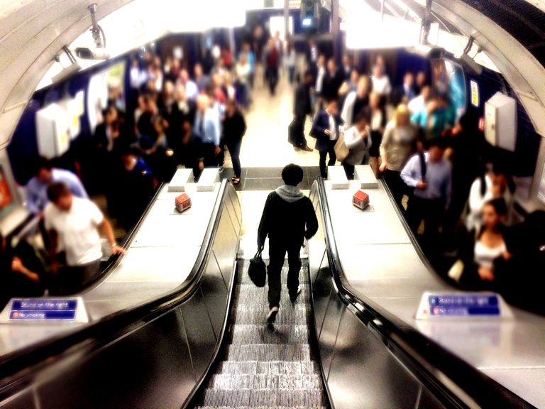 man walking off escalator in busy subway