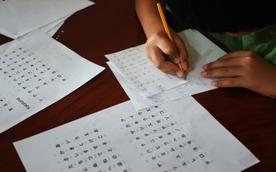 a child's hands write chinese characters