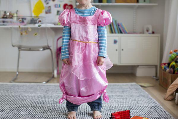 Child wearing a pink dress-up dress.
