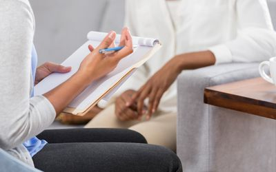 Female mental health professional talks with patient