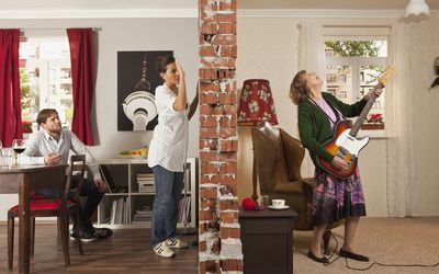 Split room view of couple annoyed by a noisy neighbor playing guitar