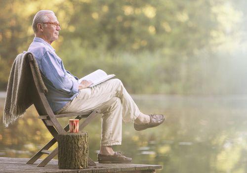 Older man reading book on dock at lake