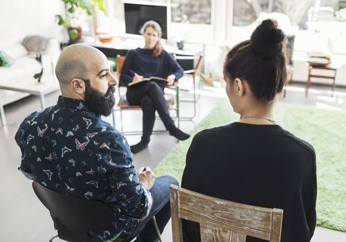 male and female sitting across from a therapist in her office
