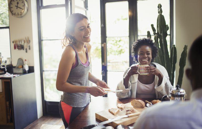 two smiling women enjoying breakfast at kitchen table