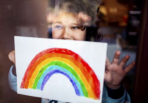 A person holding up an image of a rainbow.