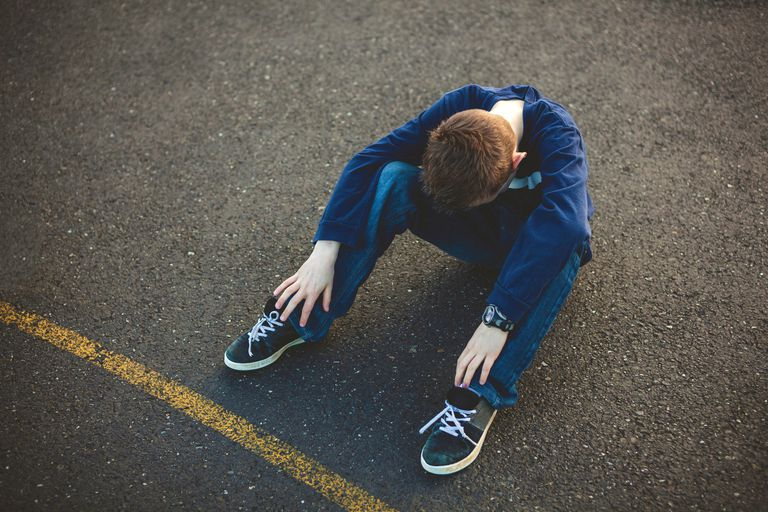 Depressed young boy with head in his knees