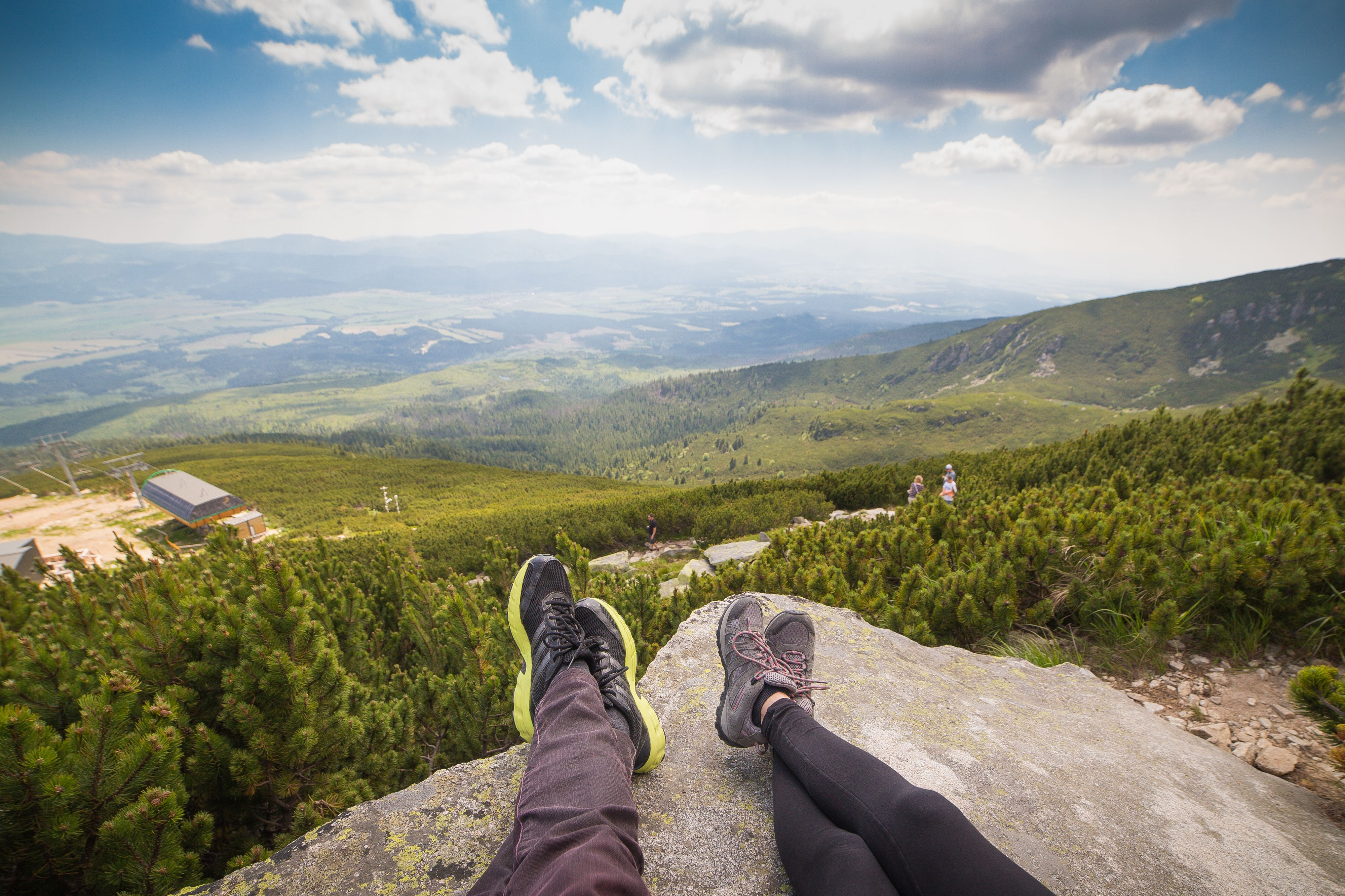 Couple's feet lying on rock at the top of a mountain
