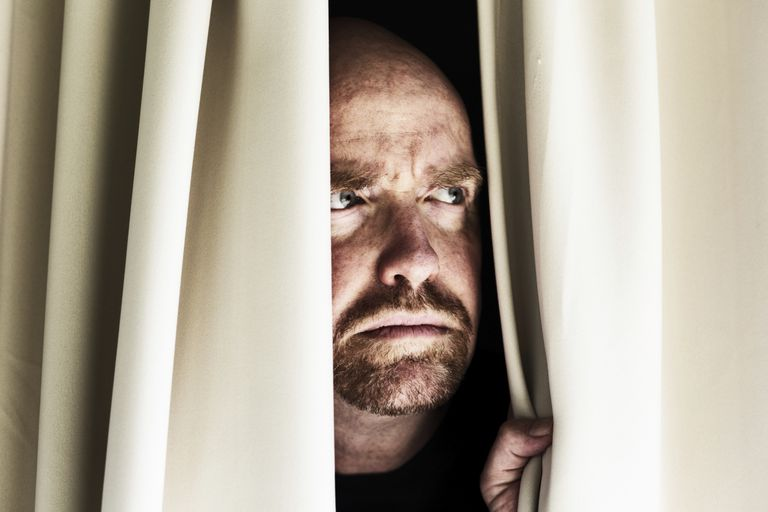 Worried man looks through closed curtains, frowning