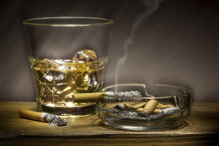 whisky glass and burnt down cigarettes