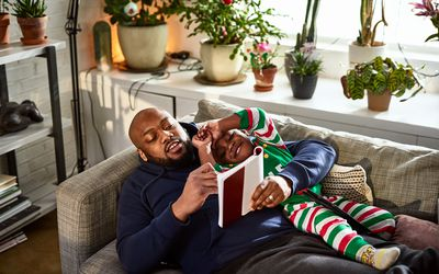 African American man and his young son read a book on the couch