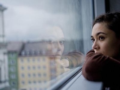 Anxious woman staring out window