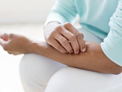 Woman picking skin on arm