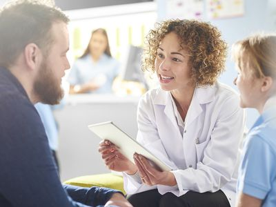 woman doctor with curly hair talking to male patient
