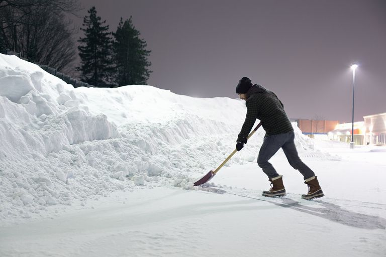 Man pushing snow with a shovel toward a snow bank at night.