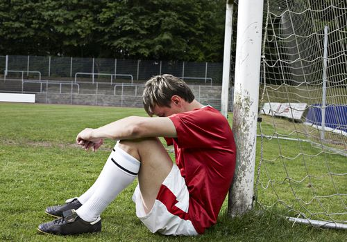 Teenager sitting on ground leaning against soccer goal post with head on his knees