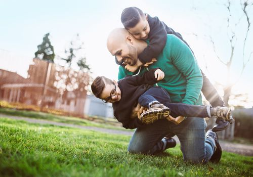 Dad wrestling with his two young sons outside