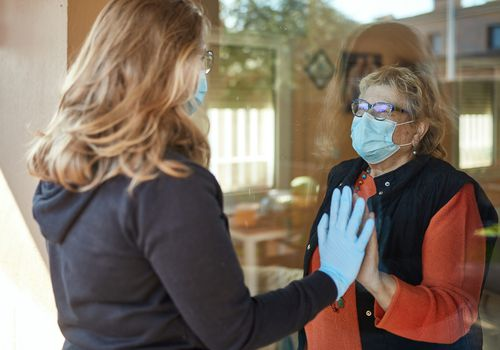 A woman wearing a mask and a blue glove touches the hand of an older woman inside a home from behind a piece of glass.