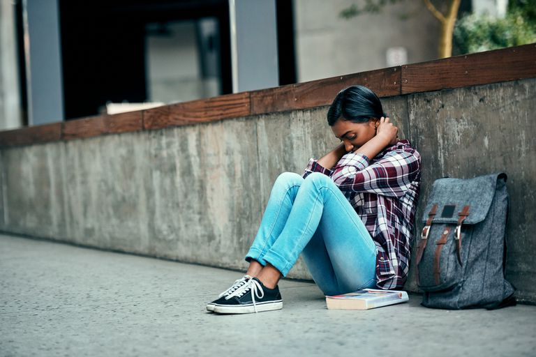 Female student sitting on the floor outside on campus