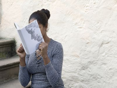 Woman reading a book with her face hidden