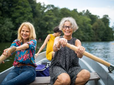 Smiling female friends rowing boat in lake