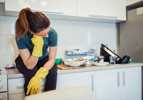 Woman with gloves in dirty kitchen