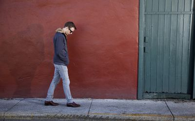 A young man in sunglasses takes a walk