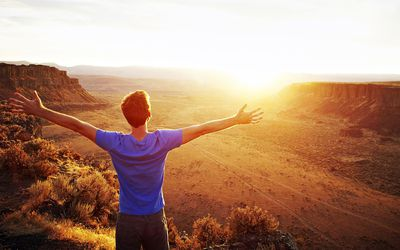 Man standing with arms outstretched looking out at desert canyon at sunset