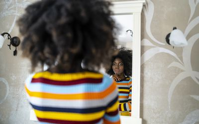 A photograph of a woman looking at her reflection in a mirror.