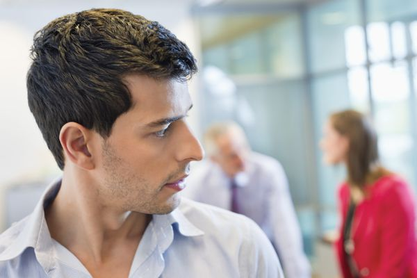 Male executive listening to his colleagues' conversation in an office