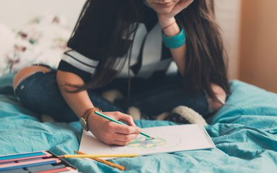 Young woman relaxing with anti-stress coloring book
