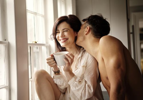 Man kissing a woman's neck while she smiles and holds a coffee cup