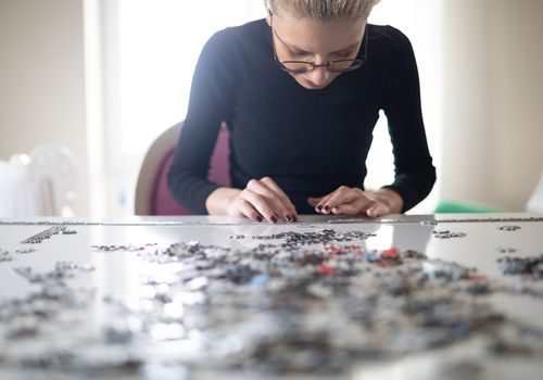 Young woman with glasses working on a puzzle.