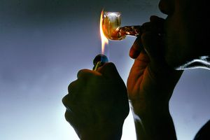 person lighting meth pipe