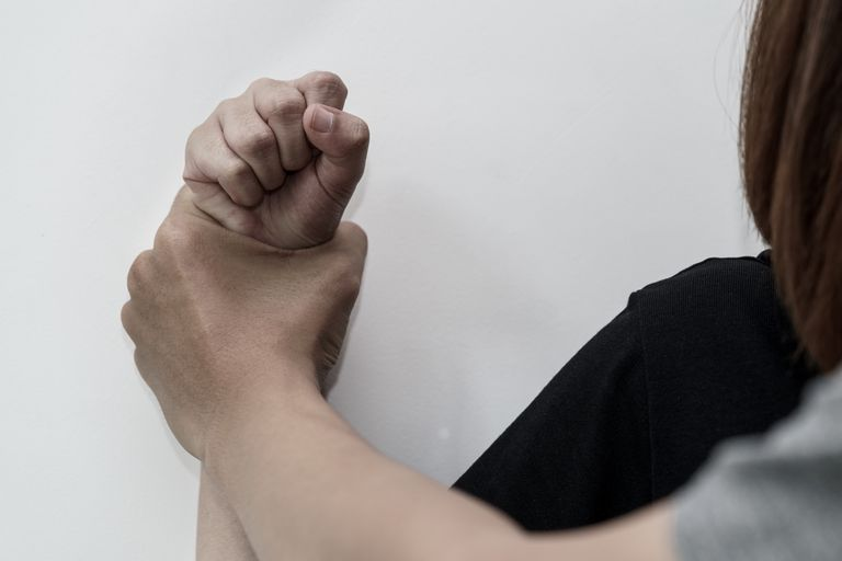 Man's hand holding a woman's clenched fist against a wall
