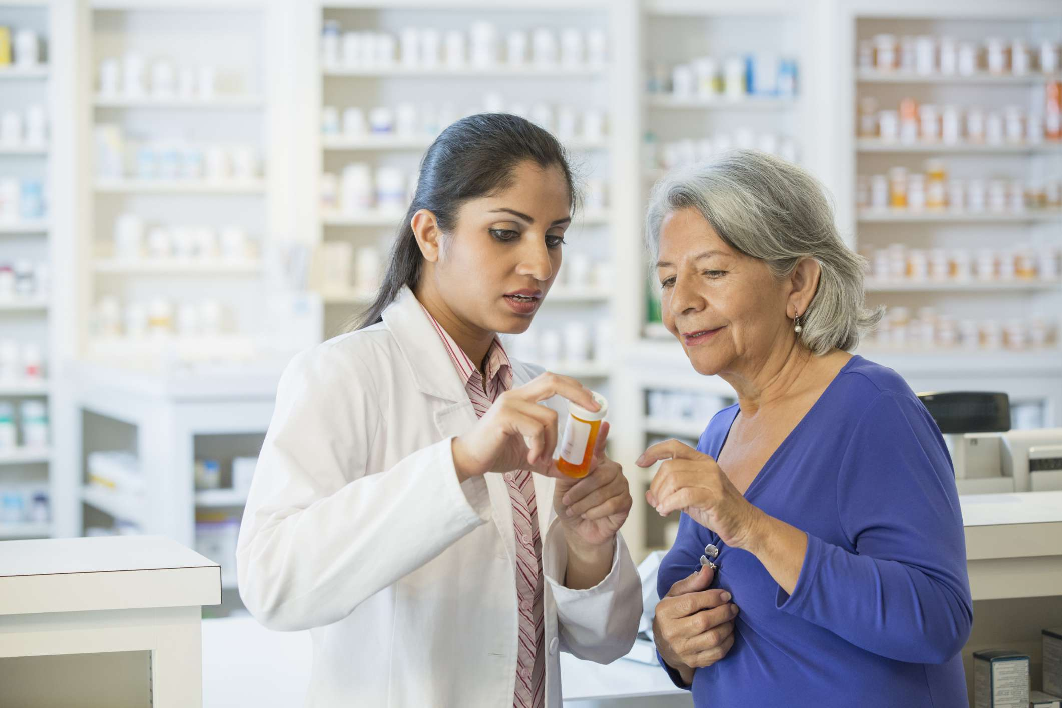 Pharmacist going over prescription label with woman