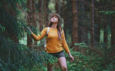 Front view of young woman on a walk outdoors in forest in summer nature, walking.