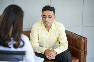 Psychologist interviewing a man about his health. Mental health and counseling concept.