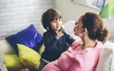 Pregnant woman blowing bubble with son