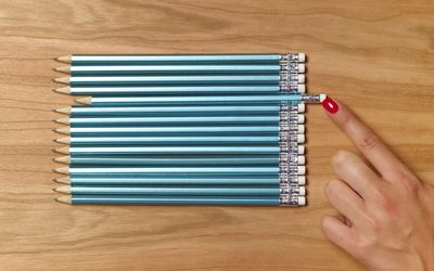 Woman organizing pencils that are all exactly the same
