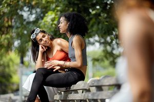 female friends sitting and talking on park bench