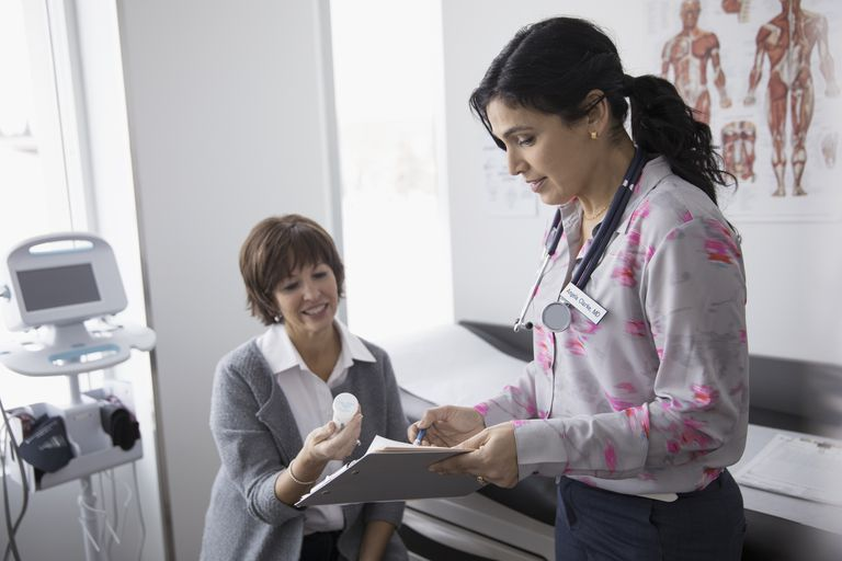 Female doctor prescribing and explaining prescription medication to patient in clinic examination room