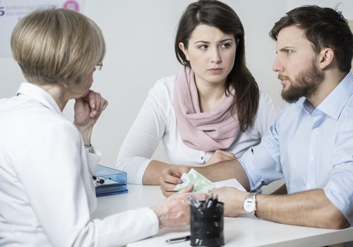 Couple with concerned expressions consulting with doctor